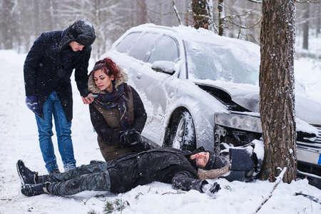 Incidente d'auto nella foresta invernale - l'uomo ferito è sdraiato sulla neve, la donna e un altro uomo stanno chiamando il 112. Archivio Fotografico