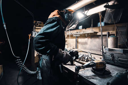 In the dark metal factory busy man is working on his workplace.