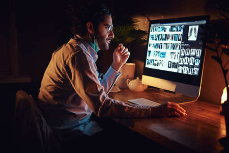 Smart medic in glasses is working with x-ray screens using a computer at dark office. Stock Photo