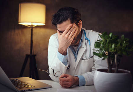 At the late evening young doctor have a lot of job and hi feels very tired and sleepy.