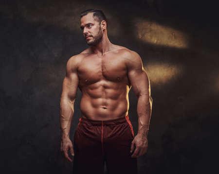 Portrait of attractive muscular bodybuilder at dark photo studio with blinks of light.