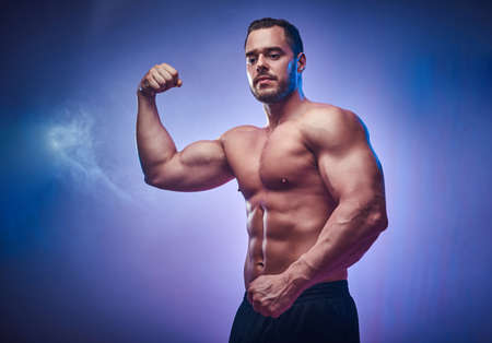 Attractive young bodybuilder is demonstrating his biceps over blue background. Stock Photo