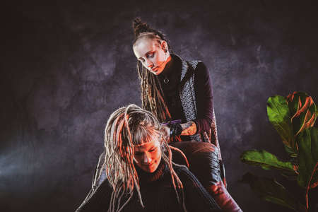 Woman with long dreadlocks is making dreads for blond girl at dark room.