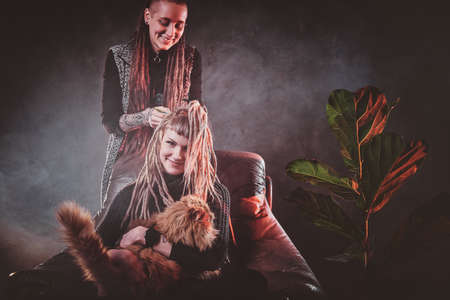 Pretty girl is holding a cat while dreadlocks master is making her new hairstyle.