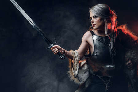 Portrait of a beautiful warrior woman holding a sword wearing steel cuirass and fur. Fantasy fashion. Studio photography on a dark background. Cosplayer as Ciri from The Witcher. Foto de archivo
