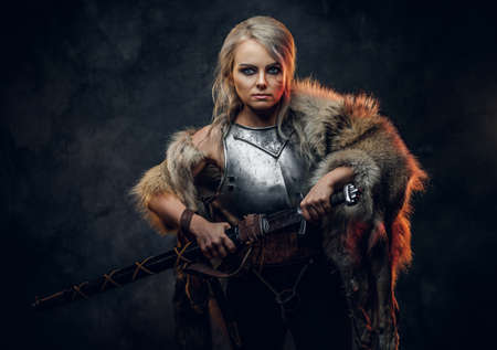 Fantasy woman knight wearing cuirass and fur, holding a sword scabbard ready for a battle. Fantasy fashion. Cosplayer as Ciri from The Witcher.