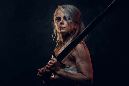 Naked fantasy woman warrior wearing rag cloth stained with blood and mud posing with a sword. Studio photo on a dark background. Cosplayer as Ciri from The Witcher