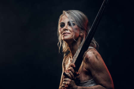 Naked Fantasy woman warrior wearing rag cloth stained with blood and mud holding a sword and smiling. Studio photo on a dark background. Cosplayer as Ciri from The Witcher