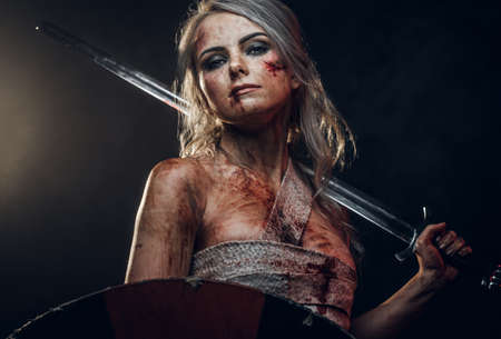 Fantasy woman warrior wearing rag cloth stained with blood and mud, holding sword and shield. Studio photo on a dark background. Cosplayer as Ciri from The Witcher