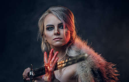 Portrait of a beautiful woman with blood stained skin holding a long sword and posing for a camera, wearing only fur. Fantasy fashion. Studio photography on a dark background. Cosplayer as Ciri from The Witcher. Standard-Bild