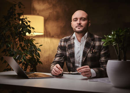Bald serious thinking european well-dressed businessman sitting in the office with soft warm lighting at a table with notebook, wearing elegant wool checkered jacket, glasses and patterned scarf.