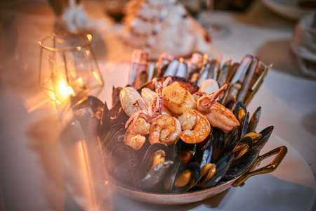 A full dinner rich ceramic bowl of prepared grilled shrimps and mussels including tiny octopus served on a white stone table next to golden candle in a soft light of a restaurant, close up 写真素材