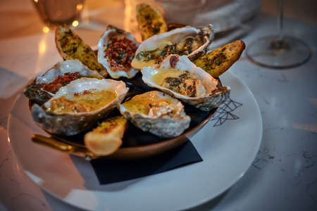 Tasty dinner golden metallic bowl of prepared oysters and crispy bread loafs with sauce and vegetable spread served on a white stone table next to candle, jellyfish in a glass stone decoration, wine glass and a wicker basket in a soft light of a restaurant, close up