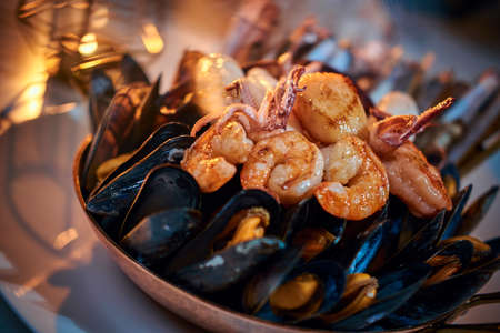 A full luxury dinner ceramic bowl of prepared grilled shrimps and mussels including tiny squids served on a white stone table next to golden candle in a soft light of a restaurant, close up
