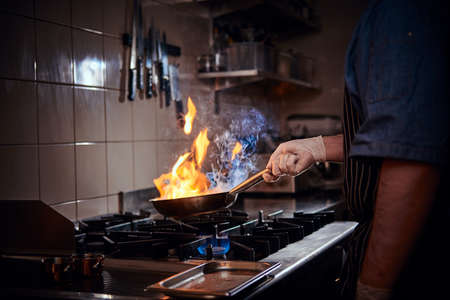 Professional chef wearing gloves and apron preparing stir-fry flambe, creating flames, holding a pan with one hand in a dark restaurant kitchen
