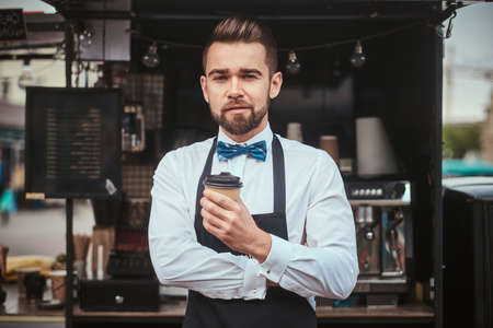 Handsome looking man barista working in a mobile coffee shop outdoors in the city emporium wearing apron and white shirt with bow tie, standing near coffee machine with arms crossed holding a paper cup of coffee