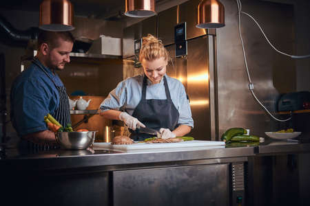 Serious male and female chefs standing in a dark kitchen next to cutting board with vegetables on it, wearing aprons and denim shirts, posing for the camera, cooking show style, working together