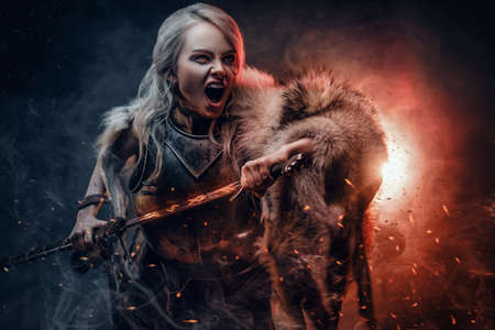 Fantasy woman wearing cuirass and fur, holding a sword and rushes into battle with a furious cry. Cosplayer as Ciri from The Witcher.