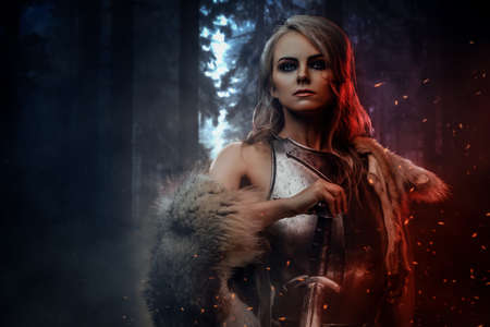 Beautiful warrior woman holding a sword wearing steel cuirass and fur in night forest. Fantasy fashion. Cosplayer as Ciri from The Witcher.