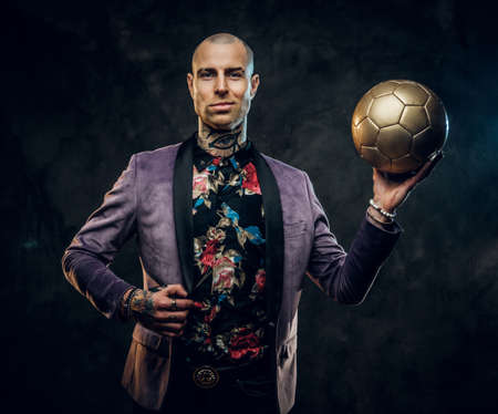 Handsome, sporty, tattooed, bald male model posing in a studio for the photoshoot wearing fashionable purple tuxedo and rose patterned shirt, looking calm on camera while holding a golden soccer ball Standard-Bild