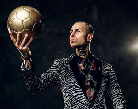 Elegant, vivid, tattooed, bald male model posing in a studio for the photoshoot wearing fashionable custom made zebra striped style tuxedo and rose patterned shirt, looking on a golden soccer ball while holding it in a hand
