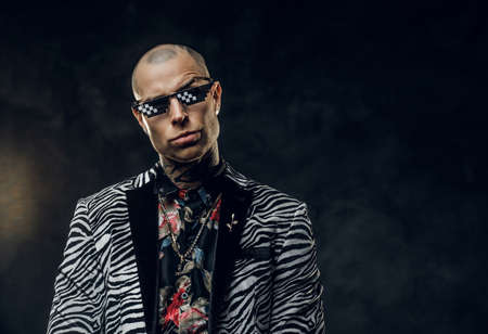Charming, masculine, tattooed, bald male model posing in a dark studio for the photoshoot wearing fashionable custom made zebra striped style tuxedo, golden chain, rose patterned shirt and black pixel glasses, dandy style, looking questioned, raising one eyebrow