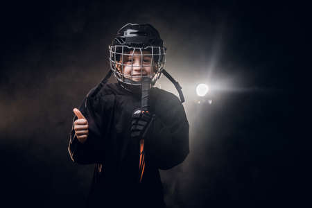 Young blonde fit boy, ice hockey player, posing in a dark studio for a photoshoot, wearing an ice-skating uniform, helmet, hockey stick, showing a gesture with his hand and smiling