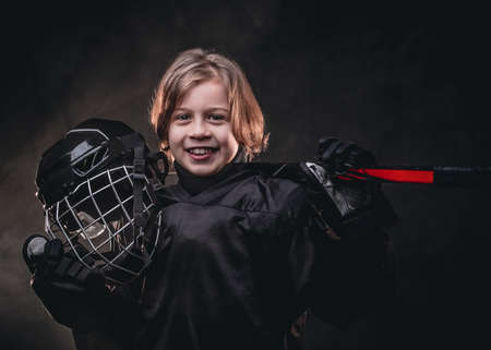 Young blonde sporty boy, ice hockey player, posing in a dark studio for a photoshoot, wearing an ice-skating uniform while holding his helmet, hockey stick and smiling on camera