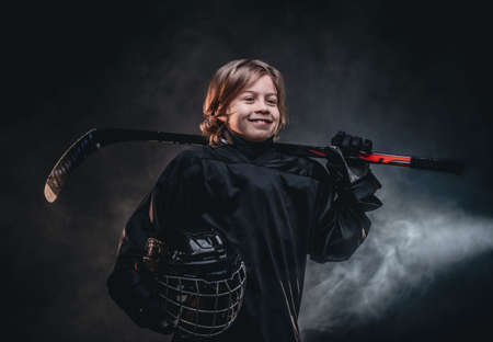 Young blonde sporty boy, ice hockey player, posing in a dark studio for a photoshoot, wearing an ice-skating uniform while holding his helmet, hockey stick and smiling