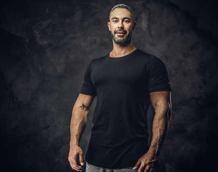 Gorgeous, adult, fit muscular caucasian man coach posing for a photoshoot in a dark studio under the spotlight wearing sportswear, showing his muscles looking calm and kind