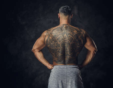 Strong and powerful masculine man posing standing with his back showing a massive mayan tattoo in a dark studio, wearing grey sportive shorts 版權商用圖片 - 140992621