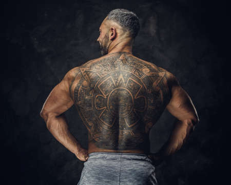 Strong and powerful masculine man posing standing with his back showing a massive mayan tattoo in a dark studio, wearing grey sportive shorts 版權商用圖片 - 140992640