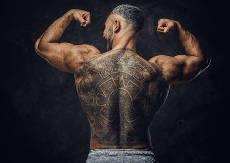 Strong and powerful masculine man posing standing with his back showing a massive mayan tattoo in a dark studio and his biceps, wearing grey sportive shorts 版權商用圖片 - 140992420