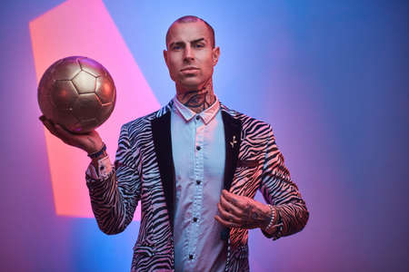 Fit, handsome, tattooed, bald male model posing in a studio for the photoshoot wearing fashionable custom made zebra striped style tuxedo and rose patterned shirt, looking on a camera, holding a golden soccer ball and looking serious