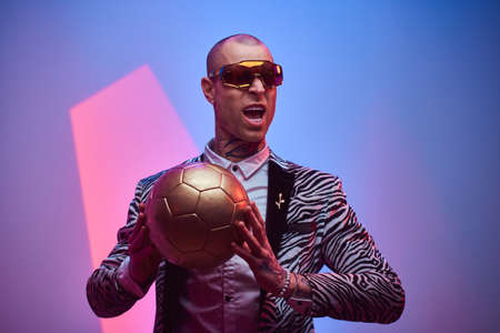 Fashionable, handsome, tattooed, bald male model posing in a studio for the photoshoot wearing fashionable custom made zebra striped style tuxedo, glasses and rose patterned shirt, holding a golden soccer ball in hands while screaming