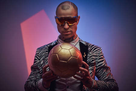 Stylish, handsome, tattooed, bald male model posing in a studio for the photoshoot wearing fashionable custom made zebra striped style tuxedo, glasses and rose patterned shirt, looking on a golden soccer ball while holding it in hands 版權商用圖片