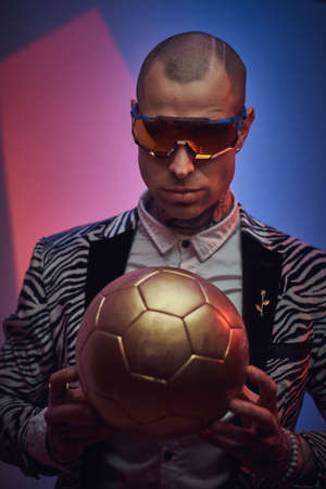 Bold, stylish, tattooed, bald male model posing in a studio for the photoshoot wearing fashionable custom made zebra striped style tuxedo, glasses and rose patterned shirt, looking on a golden soccer ball while holding it in hands, close up 版權商用圖片