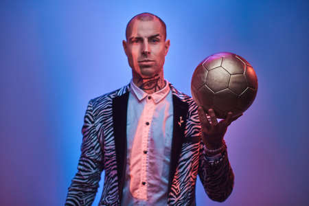 Fashionable, handsome, tattooed, bald male model posing in a studio for the photoshoot wearing fashionable custom made zebra striped style tuxedo and rose patterned shirt, looking on a golden soccer ball while holding it in a hand and smiling