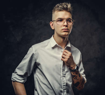 Young handsome adult student guy in a white shirt with tattoos on his hand posing in a dark studio holding a collar of his shirt. Isolated on grey background