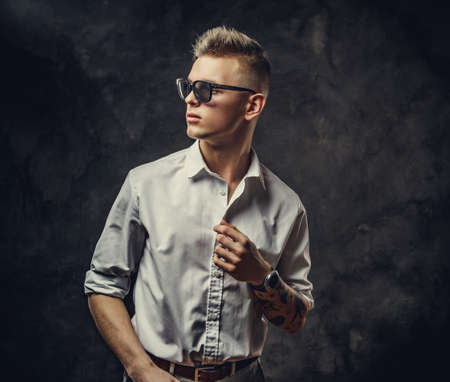 Interested and inked hipster male model posing in a studio, wearing sunglasses, white shirt, standing in front of the grey background, looking cool and confident