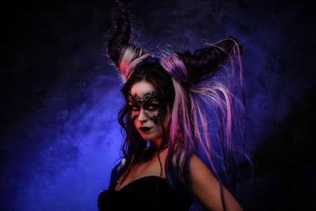 Photo portrait d'une jeune fille mystique dans un cosplay de créature magique, portant du maquillage banshee sombre et des cornes violettes, l'air effrayant entouré de fumée