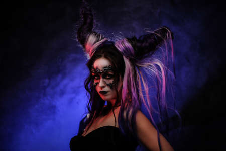 Portrait photo of a mystic young girl in a magic creature cosplay, wearing dark banshee make-up and violet horns, looking scary surrounded by smoke
