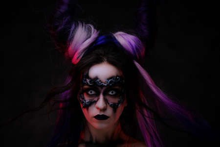 Close up photo of a banshee young girl in a magic creature cosplay, wearing dark haloween make-up, contact lenses and violet horns, looking scary Stock Photo