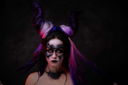 Portrait of a demonic girl wearing scary fantasy make up, white contact lenses and violet horns posing in a dark studio on a grey background, looking mystical 写真素材