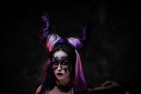 Photo of a demonic girl wearing scary fantasy make up, white contact lenses and violet horns posing in a dark studio on a grey background, looking creepy