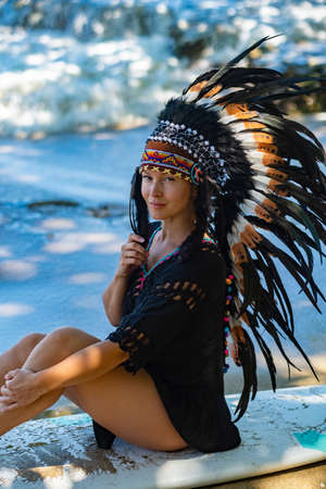 Portrait of a half-naked tribal female model posing on an ocean shore while sitting on a surfing board, wearing long ethnic indian chief headdress made of feathers