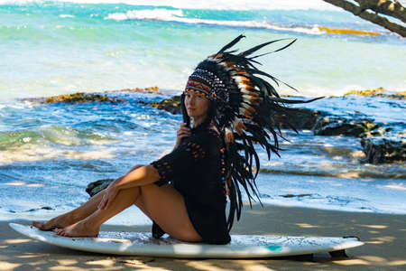 Photo of a half-nude beautiful female model posing while relaxing on a surfing board on the sand, wearing indian tribal feather headwear, looking calm and assertive