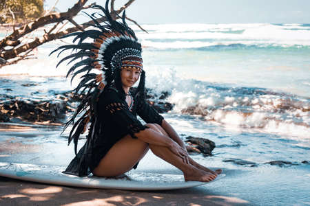 Beautiful and smiling semi-nude female wearing american indian traditional headdress, while sitting on a sea shore on a surfer board.