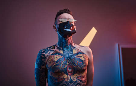Bold and rebellious male model posing in a neon studio wearing a medical mask on his face, yellow sunglasses and tattooed in a japanese irezumi style of a half-naked body, looking self-assured. Stock fotó