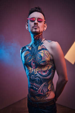 Extravagant and thin male model posing in a neon studio with a half-naked body wearing fire-shaped sunglasses and tattooed in a japanese irezumi style, looking cool and relaxed. Vertical photo